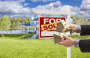 Image of man handing over cash with real estate sign